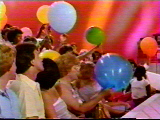 The audience members hold up their balloons