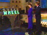 A player chooses an envelope from the 'WHEEL' sign